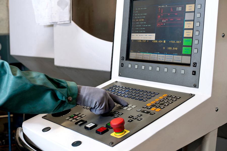 photo of hand on control panel of machine for milling industry