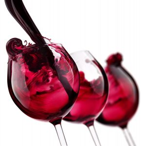 photo of pouring red wine into 3 wine glasses