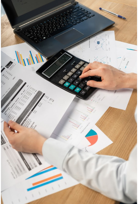 A person working on a desk with a calculator and a lot of paperwork. Representing how one can benefit from calling a Chicago CFO firm.