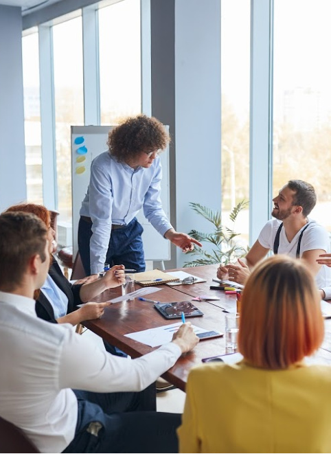 A group of business people have a meeting in a conference room, they have paperwork on the table. Representing how one can benefit from calling a CFO firm in Chicago.