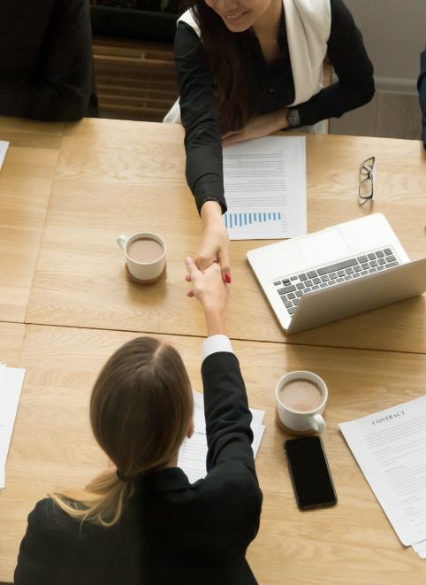 Two business women shaking hands over a table with a computer and paperwork. Representing how one can benefit from calling a Chicago CFO firm.