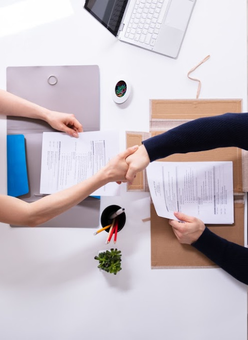 Two business people shaking hands over a work desk. Representing how one can benefit from calling a CFO firm in Chicago.