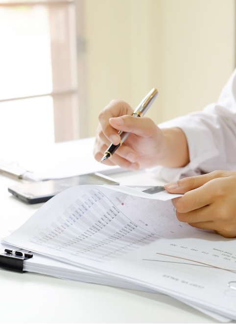 A man going over some paperwork with a pen. Representing how one can benefit from calling a Chicago CFO firm.